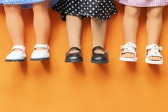 Pretty girl dolls legs wearing sandals and skirts laying on orange background b stock photos