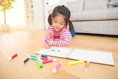 Pretty girl is drawing with felt-tip pen. Asian chinese pretty girl is drawing with felt-tip pen lying down on the wooden floor in the living room at home Royalty Free Stock Photography