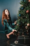 Pretty girl in a dress with gift boxes near Christmas tree, looking up with a smile. New Year concept. Luxury green, blue, golden. Colors. Home and family stock photo