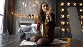 Pretty girl in dress with saxophone on sitting on windowsill in retro room near window stock video
