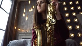 Pretty girl in dress with saxophone on sitting on windowsill in retro room near window stock footage
