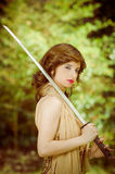 Pretty girl in a dress with vintage sword outdoors Stock Photography