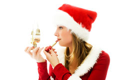 Pretty girl dressed as Santa painting her lips Stock Photography
