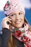 Pretty girl dressed up warm smiling using mobile Royalty Free Stock Photo