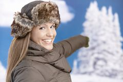 Pretty girl dressed up for winter smiling pointing Royalty Free Stock Photo