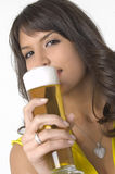 Pretty girl drinking beer from the glass. Pretty girl in yellow drinking beer from the glass Royalty Free Stock Photo