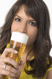 Pretty girl drinking beer from the glass. Pretty girl in yellow drinking beer from the glass Stock Image