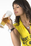 Pretty girl drinking beer from the glass. Pretty girl in yellow drinking beer from the glass Royalty Free Stock Photography