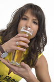 Pretty girl drinking beer from the glass. Pretty girl in yellow drinking beer from the glass Royalty Free Stock Image