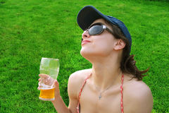 The pretty girl is drinking beer on the grass Royalty Free Stock Image