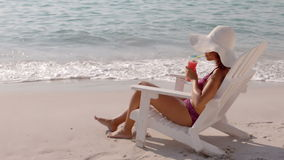 Pretty girl drinking a cocktail in the deck chair. Slow motion of a pretty girl drinking a cocktail in the deck chair stock video