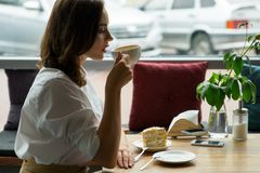 Pretty girl drinking coffee in a cafe. young woman in business clothes on a lunch break Stock Image