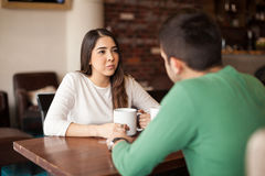 Pretty girl drinking coffee with a guy. Cute young brunette drinking some coffee while talking with a male friend at a cafe Royalty Free Stock Photography