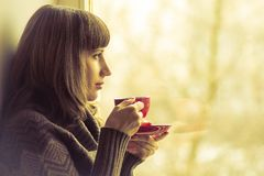 Pretty Girl drinking Coffee or Tea near Window. Warm colors toned royalty free stock photography