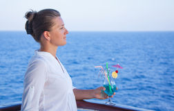 Pretty girl drinking a cold drink, admiring the sea views Royalty Free Stock Photos