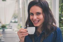 Pretty girl drinking a cup of coffee. Pretty girl with long hair drinking a cup of coffee Stock Photography
