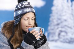 Pretty girl drinking hot tea in winter eyes closed. Pretty young girl dressed up warm for skiing wearing cap and gloves drinking hot drink eyes closed front of Royalty Free Stock Image