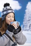 Pretty girl drinking hot tea in winter eyes closed. Pretty young girl dressed up warm for skiing wearing cap and gloves drinking hot tea eyes closed front of Stock Photo