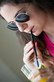 Pretty girl drinking juice. Young brunette drinking juice on the straw wearing sunglasses Stock Images