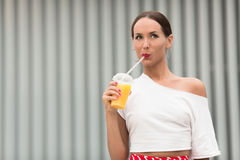 Pretty girl drinking orange juice cocktail Stock Photography