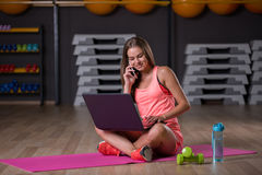 Pretty girl with dumbbells. Athlete with a laptop talking on a phone on a blurred background. Active lifestyle concept. Stock Photos