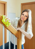 Pretty girl dusting stair railings Stock Image