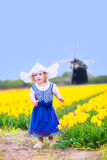 Pretty girl in Dutch costume in tulips field with windmill. Adorable curly toddler girl wearing Dutch traditional national costume dress and hat playing in a Royalty Free Stock Photo