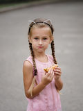A pretty girl is eating a cheeseburger on a blurred street background. A little girl with a sandwich. royalty free stock images