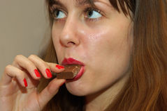 Pretty girl eating a chocolate bar Stock Image