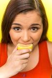 Pretty girl eating fresh lemon. Stock Photos