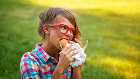 Pretty girl eating a hot dog. Royalty Free Stock Photos