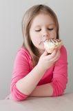 Pretty girl eating ice cream. Indoor portrait of a pretty girl eating ice cream royalty free stock image