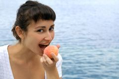 Pretty girl eating peach Stock Photo