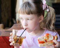 Pretty girl eating a piece of a pizza and drinking a juice stock photography