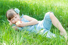 Pretty girl eating red apple on grassland. Happy kids concept. Stock Images