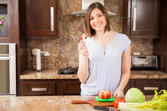 Pretty girl eating some apple. Beautiful young woman eating some apple slices after using a slicer in the kitchen Stock Images