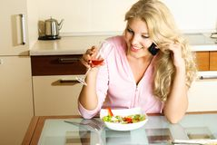 Pretty girl eating and taking on the cellphone Stock Photos
