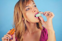 Girl eating tasty macaroon cookies Royalty Free Stock Image