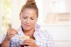 Pretty girl eating yoghurt at home dieting Royalty Free Stock Images