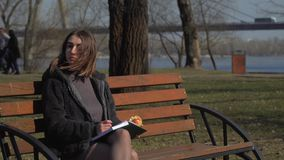 Pretty girl eats apple on the bench in park, and makes notes in notebook. Young girl sits on bench in park and writes in her notebook. Pretty female is relaxing stock footage