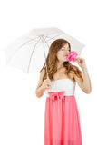 Pretty girl in elegant dress standing under umbrella smelling ro Royalty Free Stock Photography
