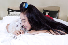 Pretty girl embrace her dog on bed Royalty Free Stock Photo