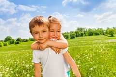 Pretty girl embraces boy on a meadow Royalty Free Stock Photo