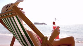 Pretty girl enjoying a cocktail in the deck chair. Slow motion of a pretty girl enjoying a cocktail in the deck chair stock footage