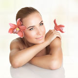 Pretty girl enjoying dayspa. Pretty girl with orchid flowers in the head and hand enjoying dayspa, body care, healthy lifestyle, beauty treatment in a spa salon Royalty Free Stock Photo