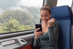 Excited woman holding a smartphone and winning on line on the train journey stock photos