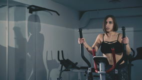 Pretty girl exercises on stepper in the gym in 4K stock video footage