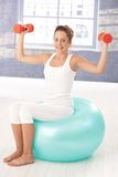 Pretty girl exercising with dumbbells on fitball Stock Photo