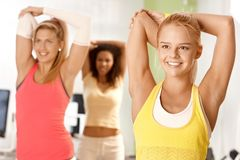 Pretty girl exercising in group. Smiling, stretching Stock Photos