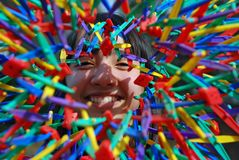 Pretty Girl Explosion of Color. Pretty girl smiling and playing with a colorful, expandable toy ball, giving a 3-D, explosion of color, motion effect Royalty Free Stock Photo